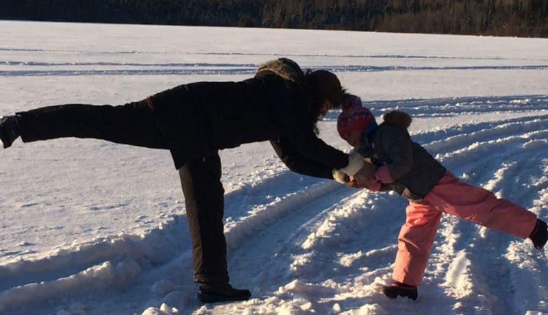 Femme et fillette faisant du yoga l'hiver, dans la neige