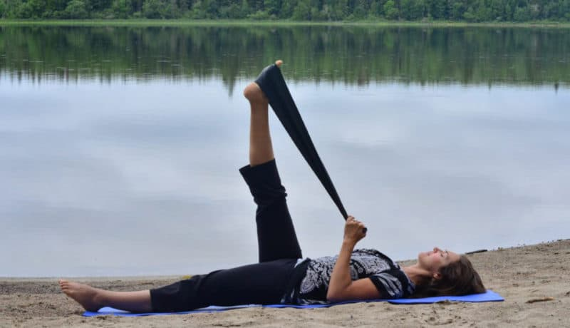 Femme faisant des étirements avec une bande élastique sur le bord d'un lac
