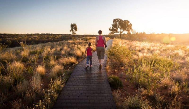 Femme et enfants marchant sur un sentier au coucher de soleil
