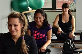 3 jeunes femmes effectuant des exercices sur reformer