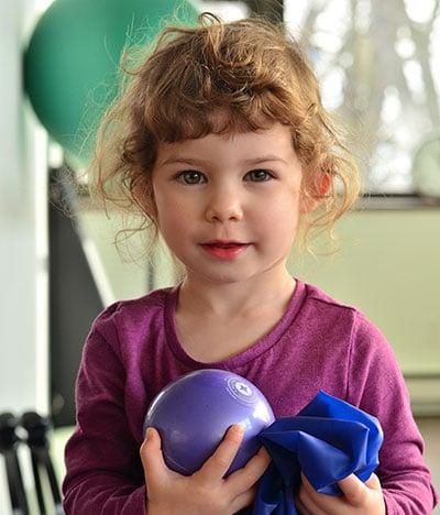 fillette avec balle et élastique de fitness