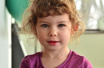 photo portrait d'une fillette aux cheveux chatains bouclés