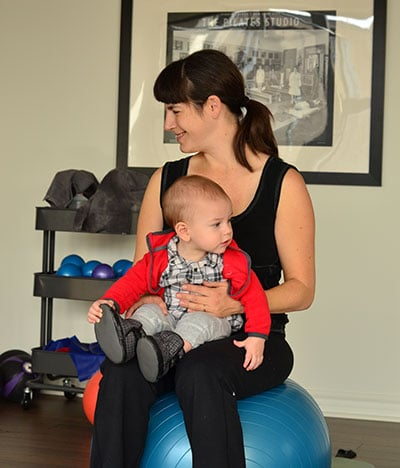 smiling mom sitting on ball with baby in arms