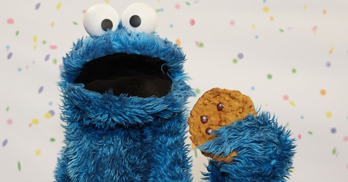 Monstre bleu avec biscuit aux pépites de chocolat dans la main