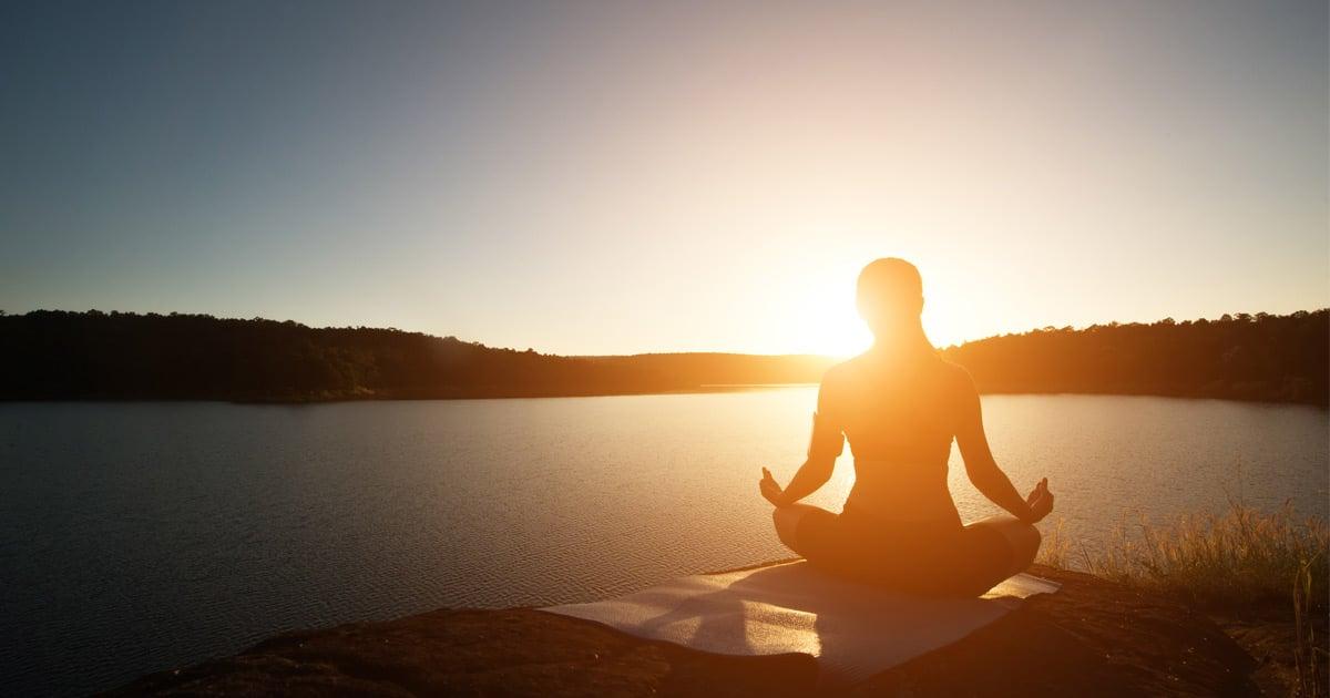 femme faisant de la méditation devant un lac au coucher du soleil